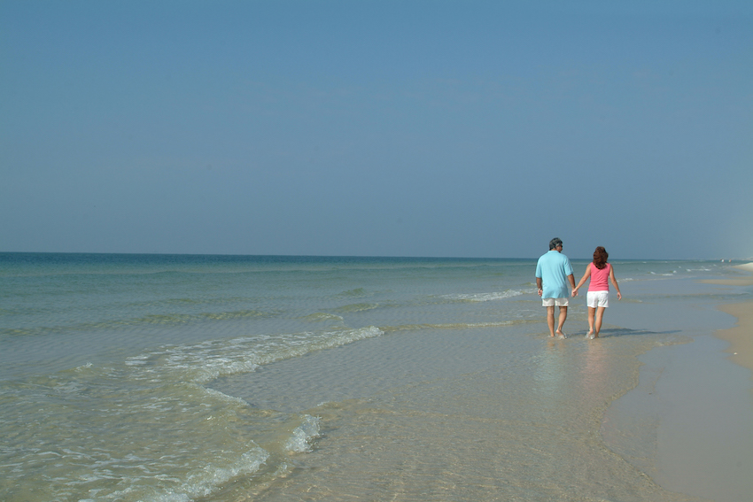 Couple walking in the water on the beach